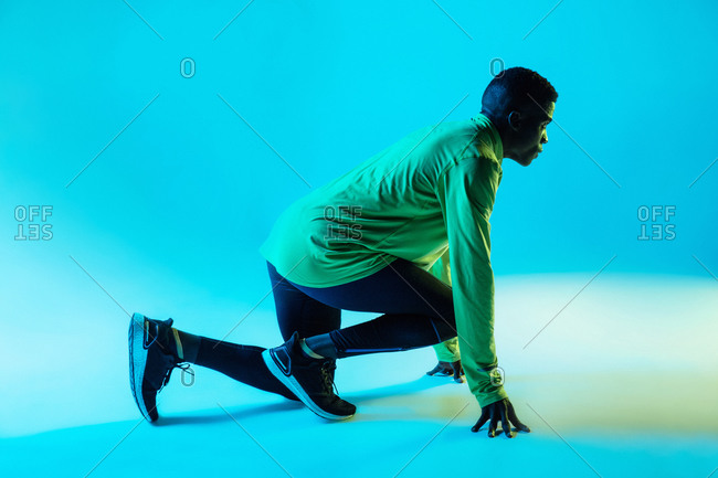 Full body side view of young African American male athlete in trendy sportswear and sneakers in low start position ready for sprint in studio with neon lights