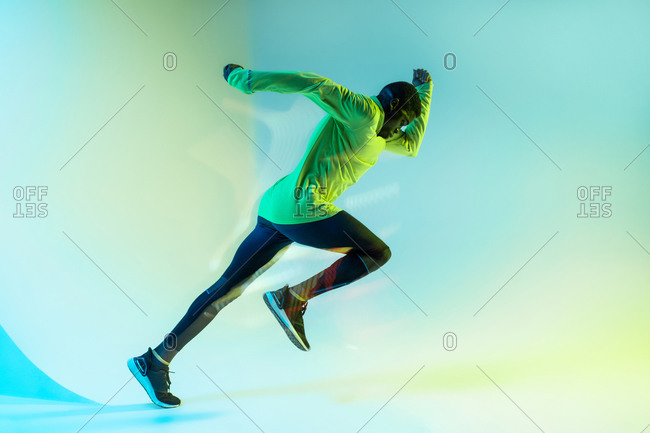 Full body side view of young African American male runner in colorful tracksuit sprinting from start position in studio with bright neon illumination
