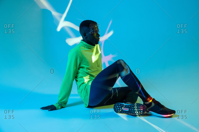 Full body side view of strong young African American male athlete in stylish colorful tracksuit and sneakers sitting on floor in blue studio with neon lights