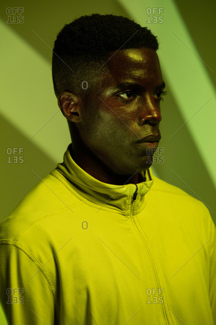 Young African American male athlete in sportswear looking away while standing under green neon illumination near corner with striped shadows in studio