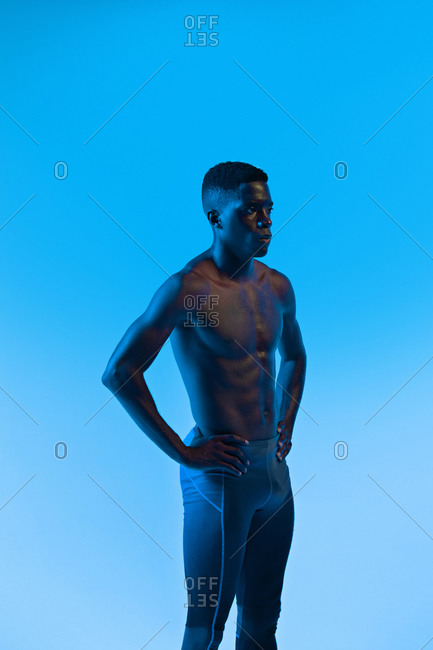 Serious young muscular African American sportsman with naked torso keeping hands on waist and looking away while standing in neon lights against blue background in studio