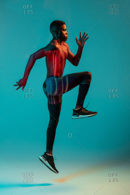 Full body side view of young African American male runner in colorful tracksuit sprinting jumping in studio with bright neon illumination