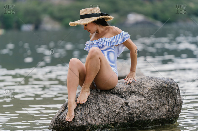 Full body of charming elegant young pregnant female in stylish swimsuit and straw hat sitting on stone in river water in summer day
