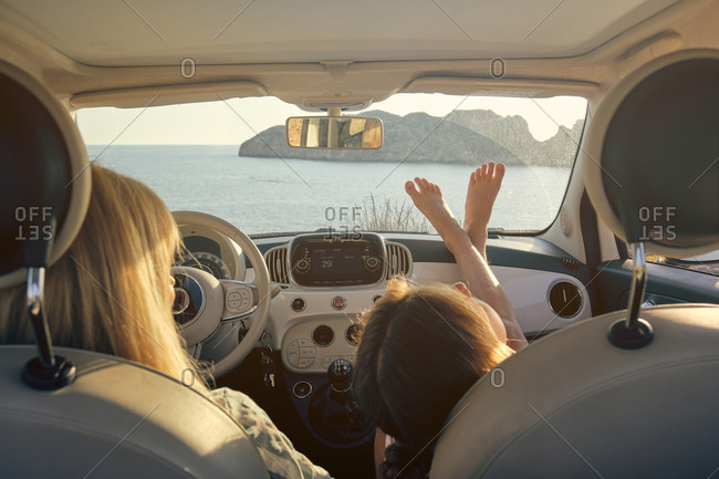Interior of a car with mother and daughter sitting inside facing the sea