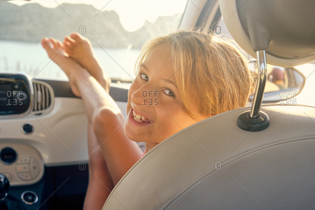 Blonde girl sitting in a car with her feet in front of the car and turning to facing the camera with the sea on the background