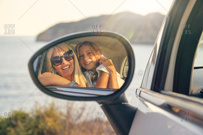 Car mirror with the image of a blond mother and daughter hugging and looking at the mirror in front of the sea