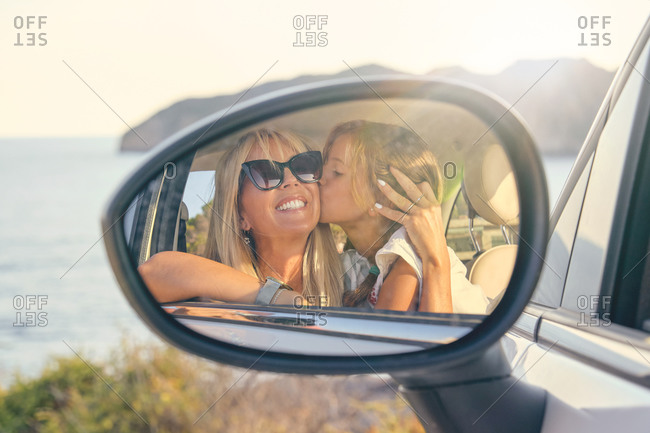 Car mirror with the image of a blond daughter kissing and hugging her mother and looking at the mirror in front of the sea