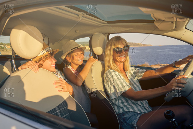 Blonde mother with sunglasses driving a car with the two children with hats in the back seats expressing happiness while laughing with the sea on the background
