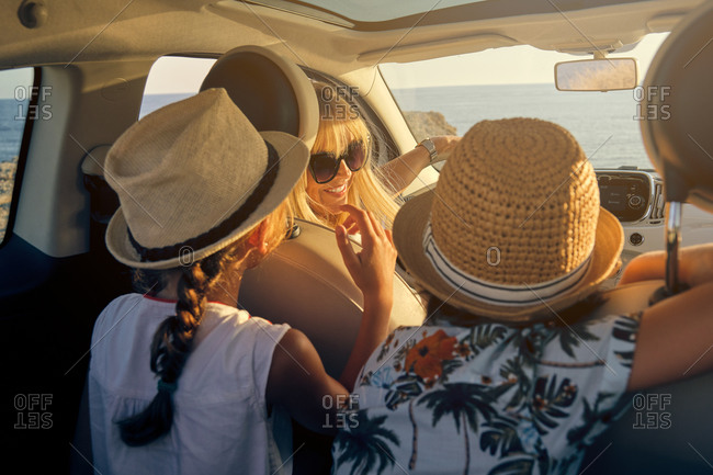 Blonde mother with sunglasses sitting in a car and looking at her children sitting in the back seats that wearing straw hats while are parked in front of the sea