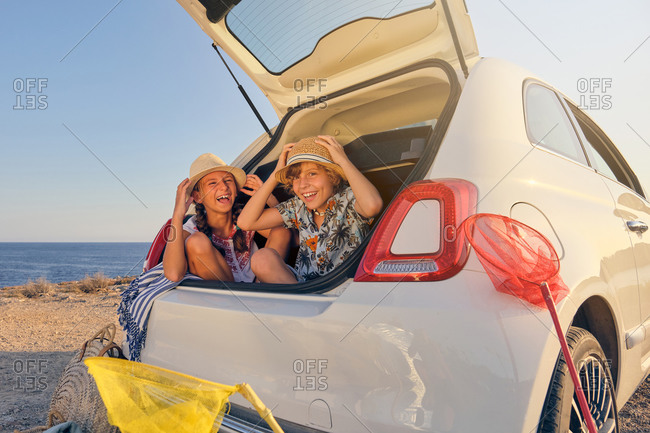 Two children sitting inside the trunk of the car making jokes while touching the straw hat with baskets of objects for the beach next to the car with the sea in the background