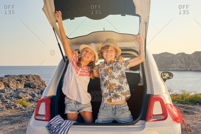 Two children bending inside the trunk of the car with their hands raised in a gesture of victory while wearing a straw hat with baskets of objects for the beach next to the car with the sea in the background