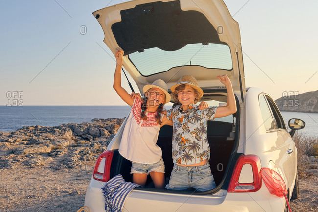 Two children bending inside the trunk of the car with their hands raised in a gesture of victory while facing the camera and wearing a straw hat with baskets of objects for the beach next to the car with the sea in the background