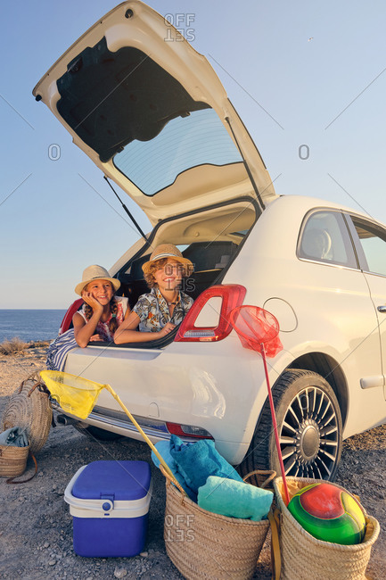 Vertical photo of a blonde girl inside the trunk of a white car making a wait gesture with a happy expression next to a boy in a straw hat and the sea in the background