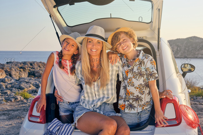 Mother embracing her two children in straw hats and summer clothes sitting in the trunk of a white car with the sea on the background