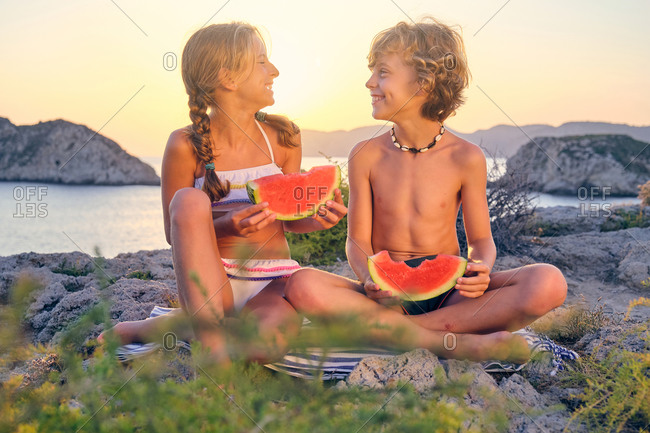Two children smiling and eating watermelon sitting on a blue and white striped towel on a rock while looking each other with the sea on the background during sunset