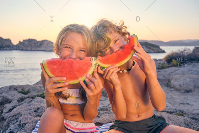 Two children playing with a piece of watermelon imitating a smile with it sitting on some rocks in front of the sea during the sunset