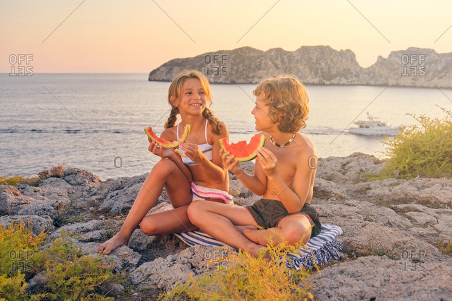 Two children smiling and eating a piece of watermelon sitting on the rocks in front of the sea with a boat during the sunset