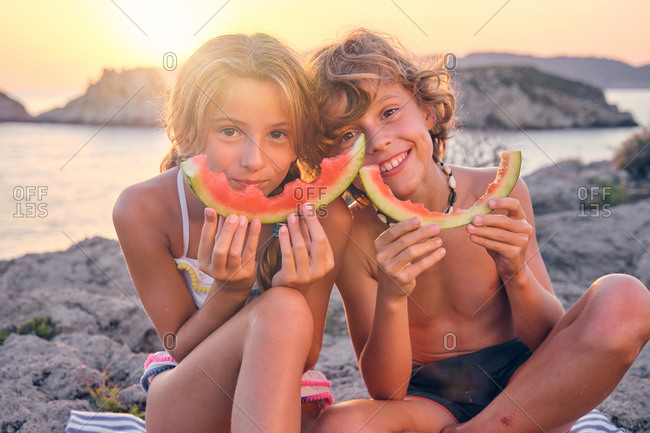 Two children playing with the residue of a piece of watermelon imitating a smile with it sitting on some rocks in front of the sea during the sunset