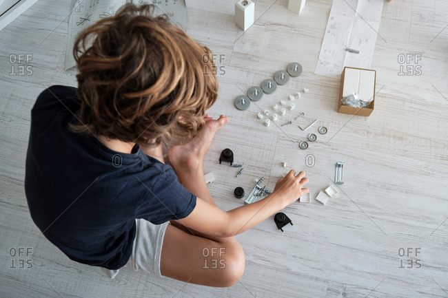 From above of unrecognizable boy sitting on floor and examining pieces for furniture assembling at home