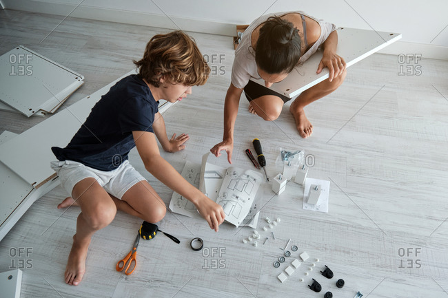 From above unrecognizable preteen boy sitting on floor with new furniture parts and examining paper instruction while helping unrecognizable mother to fix wardrobe in room with dog lying nearby
