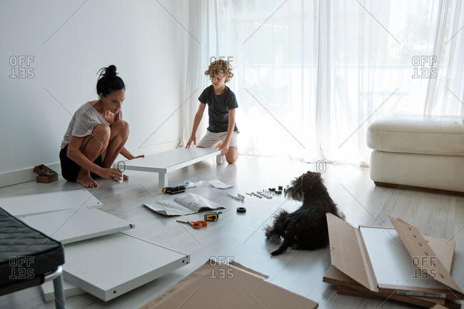 Preteen boy helping mother with fixing new wardrobe in light room with dog