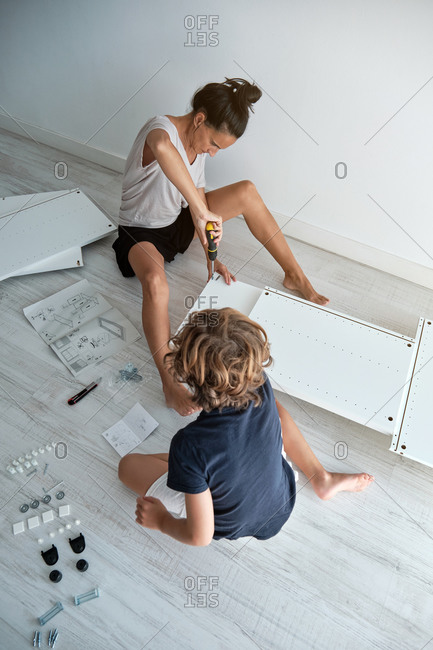 From above focused young female in casual wear with screwdriver fixing wooden board of new furniture in light apartment with son sitting nearby