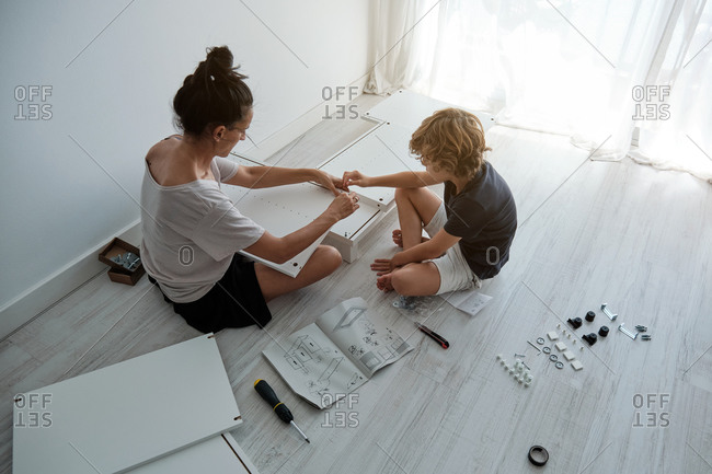 From above of young female with son using paper instruction and fixing details of wooden wardrobe while assembling furniture together in new home