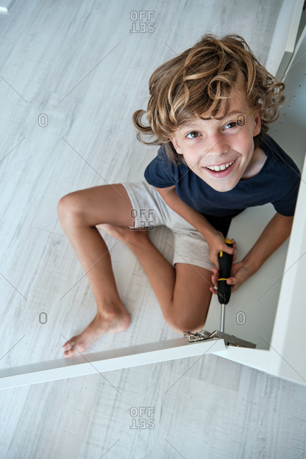 From above of cheerful preteen boy sitting on floor and looking at camera while mounting details of new wardrobe with screwdriver