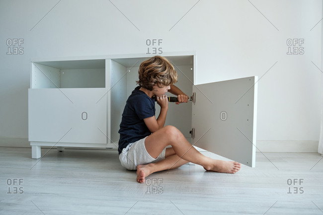 Full body side view of focused preteen boy sitting on floor and installing door of wooden cabinet with screwdriver in new light room at home