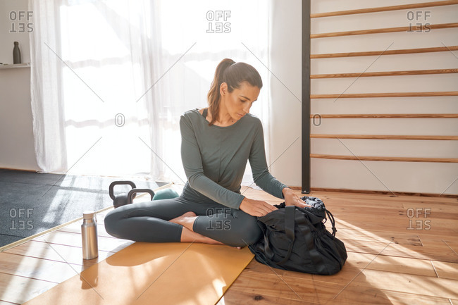 Calm female in sportswear sitting on mat and preparing for yoga practice in studio