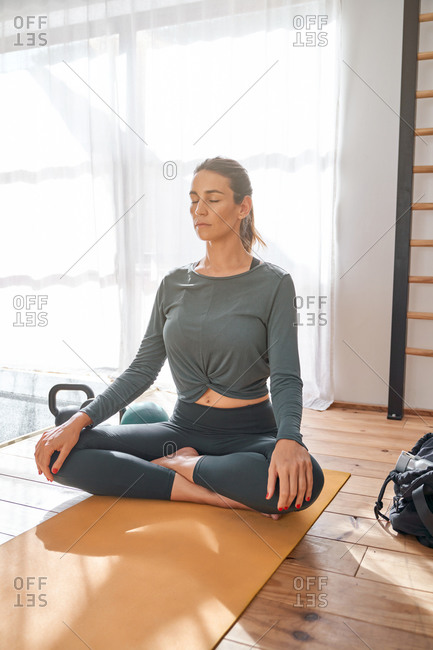 Peaceful female sitting on mat in Padmasana with crossed legs and practicing yoga with closed eyes
