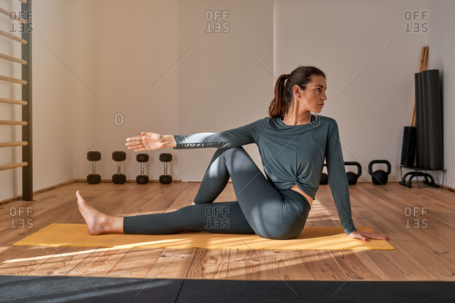 Side view of flexible female in sportswear stretching body and doing yoga on mat in gym