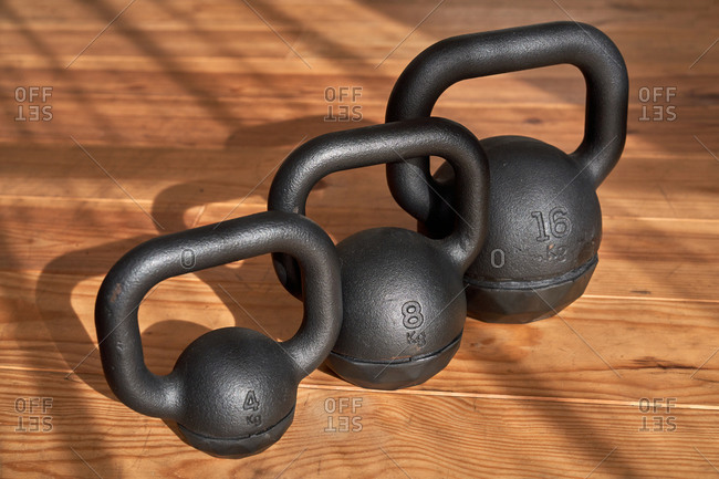 From above of various metal kettlebells placed in row on floor in contemporary gym