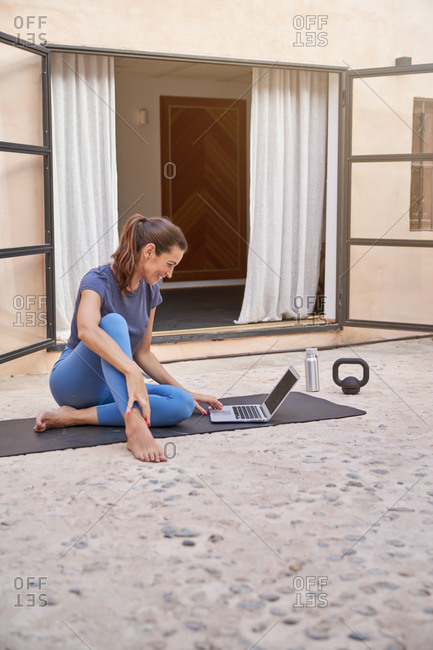 Side view of cheerful female athlete sitting on mat on terrace and picking online tutorial for workout