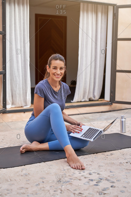 Cheerful female athlete sitting on mat on terrace and picking online tutorial for workout looking at camera