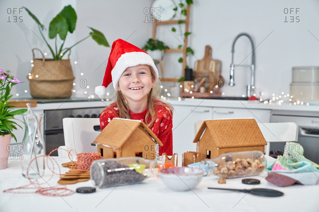 Cheerful little girl in red Santa hats sitting at table and decorating gingerbread houses with icing while preparing for Christmas celebration at home looking at camera