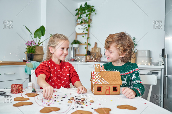 Cheerful little boy and girl in red Santa Claus hats smiling and looking at each other while making Christmas gingerbread houses in home kitchen