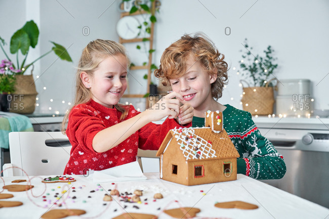 Cheerful little boy and girl in red Santa Claus hats smiling while making Christmas gingerbread houses in home kitchen