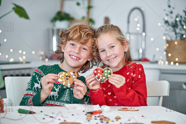 Positive little sister and brother in colorful knitted sweaters demonstrating handmade decorated Christmas cookies in shape of heart while sitting at table in cozy kitchen at home