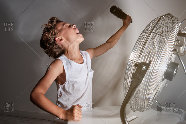 Child with a white shirt with a raised arm holding a hairbrush that mimics a microphone singing in front of a running fan in a room