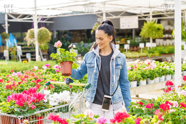 Young girl buying flowers and seasonal plants at a nursery