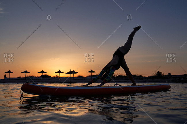 Side view of silhouette of calm female surfer practicing yoga in Eka Pada Adho Mukha Svanasana while standing on surfboard in sea during sunset
