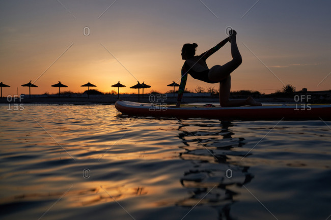 Side view of silhouette of calm female surfer practicing yoga on surfboard in sea during sunset