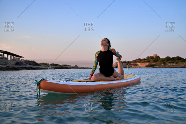 Relaxed female surfer in swimsuit sitting on board in King Pigeon pose while practicing yoga during sunset