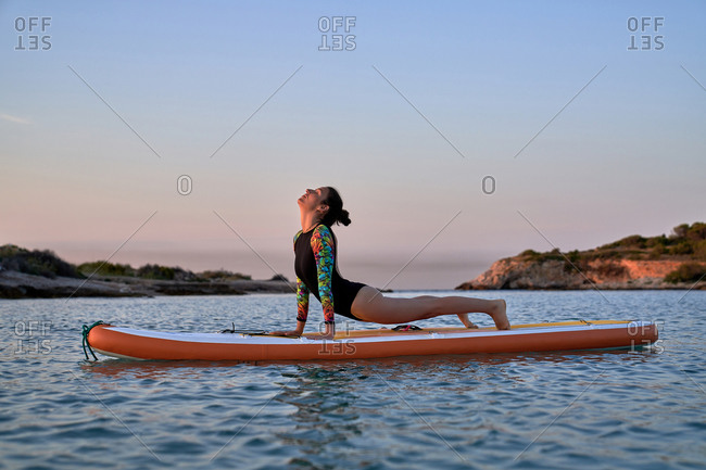 Side view of woman surfer practicing yoga on surfboard in sea during sunset