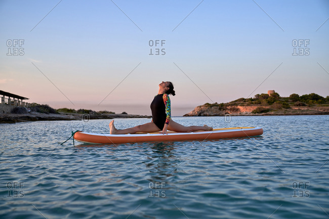 Side view of flexible female in swimsuit performing Front Splits while practicing yoga on paddle board and looking up