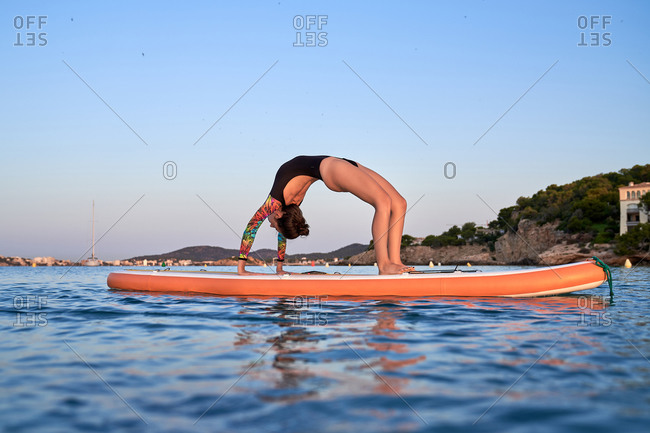 Side view of unrecognizable female in swimsuit standing in Urdhva Dhanurasana on paddleboard in sea and doing yoga during sundown