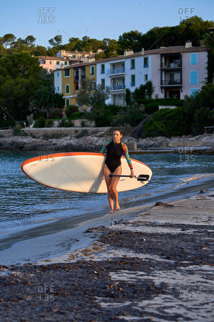 Slim woman in swimsuit walking along sandy shore with paddleboard and paddle during sunset