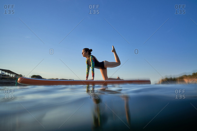 Woman surfer practicing yoga on surfboard in sea during sunset