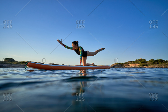 Concentrated female surfer practicing yoga in Utthita Cakravakasana while balancing on paddleboard in sea during sunset